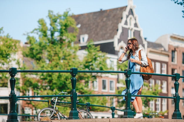 Young woman on european vacation in amsterdam at the bridge