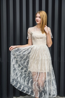 Young woman in evening dress posing on city street, dark wall background