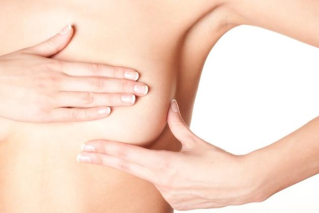 암에 대한 가정 방법으로 그녀의 유방을 검사하는 젊은 여성