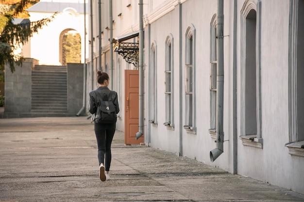 Молодая женщина изучает архитектуру. студентка гуляет по городу. туристическое путешествие по старинным дворам. вид сзади.