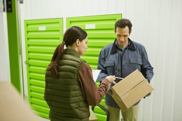 Young woman examining document and passing the box to her colleague while they working in warehouse