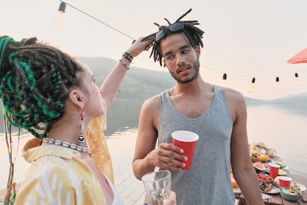 Young woman examining the hairstyle of her boyfriend while they spending time outdoors