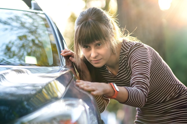 Young woman examining new car at dealer sales shop before purchase.