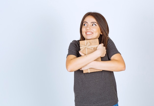 Молодая женщина взволнована подарочной коробкой.