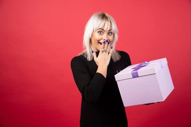 Молодая женщина взволнована подарком на красном фоне