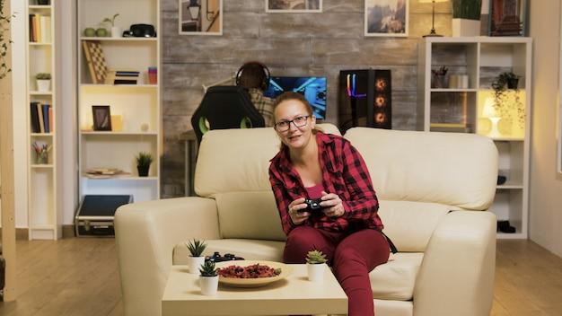 무선 컨트롤러를 사용하여 거실에서 비디오 게임을 하는 동안 승리한 후 흥분한 젊은 여성. 백그라운드에서 남자 친구입니다.
