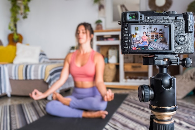 若い女性が自宅でピラティスをやっていて、デジタルカメラで彼女に録音してトレーニングを教え、ウェブクラスのコンテンツクリエータービジネスを無料で健康的なライフスタイルの人々のコンセプトを生み出しています