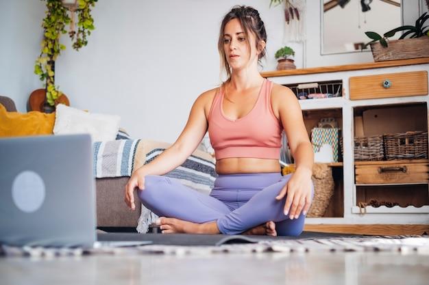自宅でヨガをし、自分のラップトップコンピューターを見て、ワークアウトコンテンツクリエータービジネス無料の健康的なライフスタイルの人々の概念を学ぶまたは教える若い女性