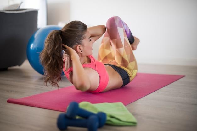 Молодая женщина, тренирующаяся дома. здоровый образ жизни стал моей повседневной рутиной