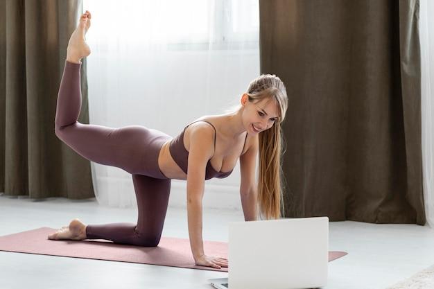 Молодая женщина, тренирующаяся дома на коврике