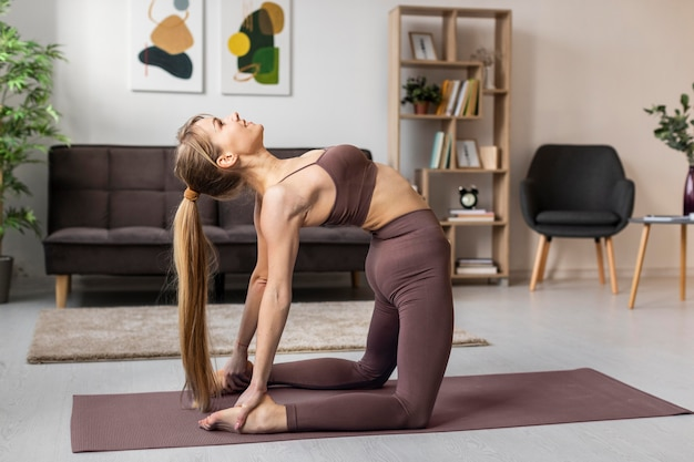 매트에 집에서 운동하는 젊은 여자