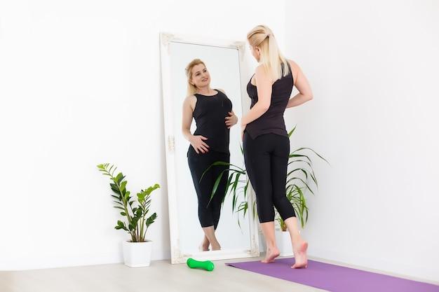 Молодая женщина тренируется дома, растягивая ноги.