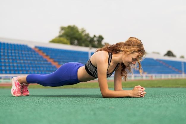 경기장에서 운동하는 젊은 여자
