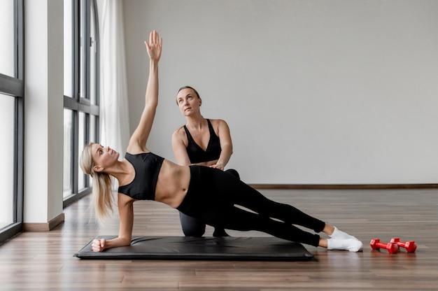 전신 운동을 하 고 체육관에서 운동하는 젊은 여자