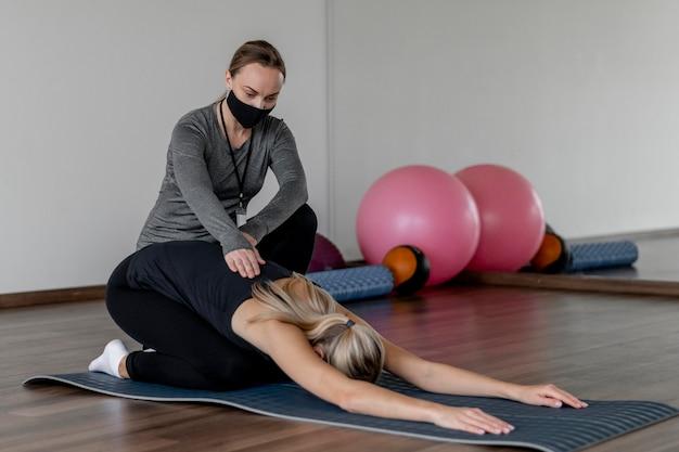 코치 도움을받는 체육관에서 운동하는 젊은 여자