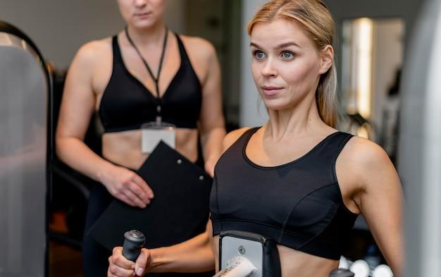 ジムのミディアムショットで運動する若い女性