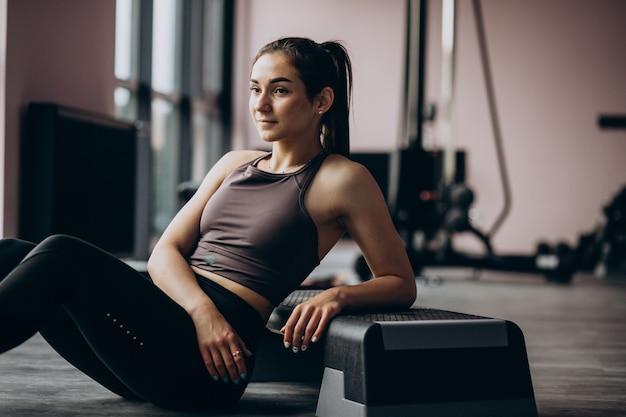Молодая женщина, осуществляя в тренажерном зале с весом