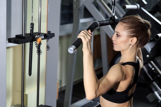 ジムでマシンに戻って運動し、筋肉を曲げる若い女性-筋肉アスリートボディービルダーフィットネスモデル