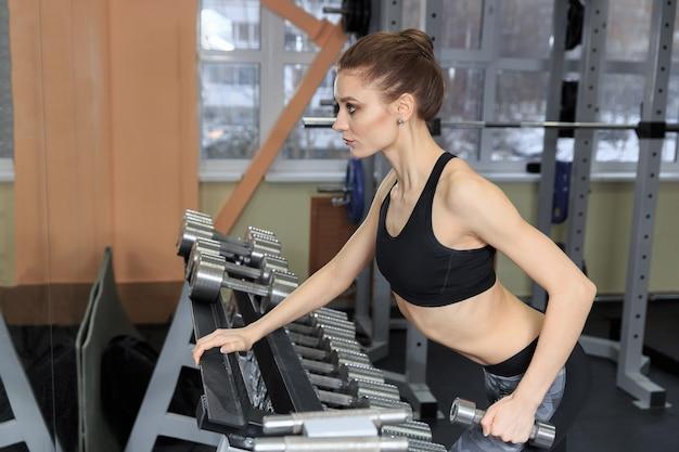 체육관에서 아령으로 다시 운동하고 근육을 구부리는 젊은 여성 - 근육질 운동 보디 피트니스 모델