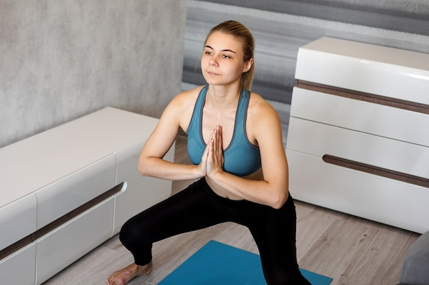 Young woman exercising and doing squats in the living room at home