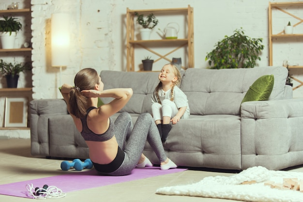Young woman exercising fitness at home with her daughter
