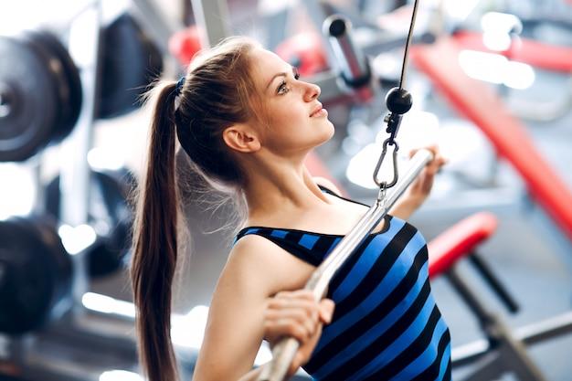 운동하는 젊은 여자. 체육관에서 피트니스 운동.
