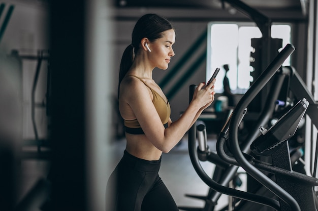 Young woman exercising at gym on elliptical