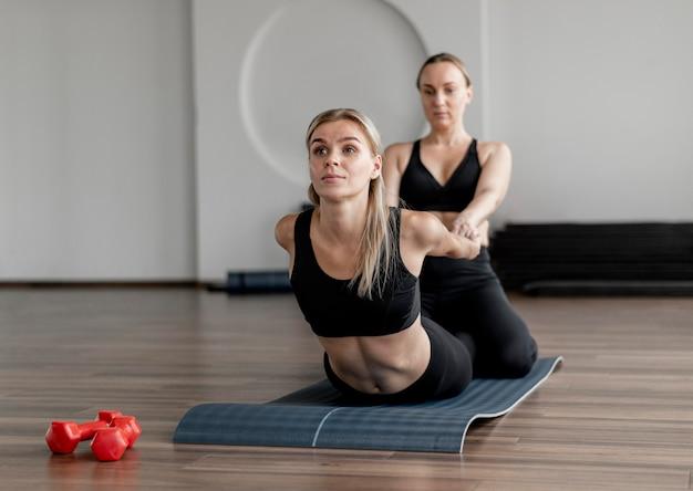 Giovane donna che si esercita in palestra stretching