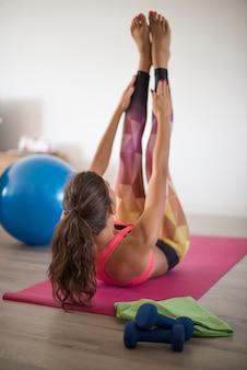 Giovane donna che esercita a casa. questo è uno degli esercizi più difficili