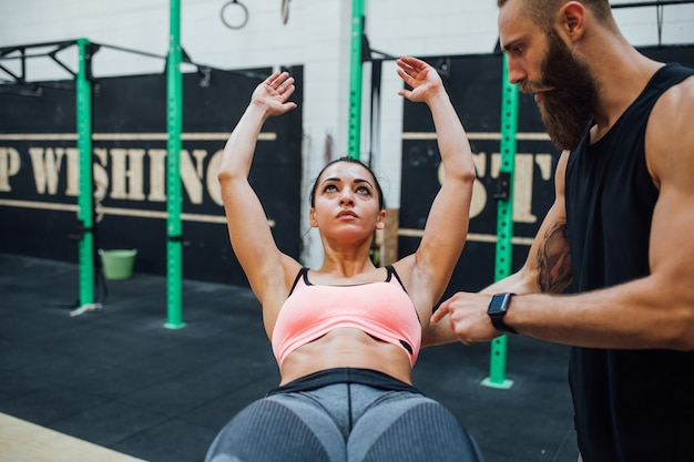 Young woman exercising indoor gym with personal trainer