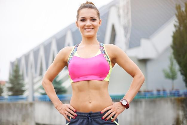 屋外で運動する若い女性。魅力的な若い女性のアスリートボディ