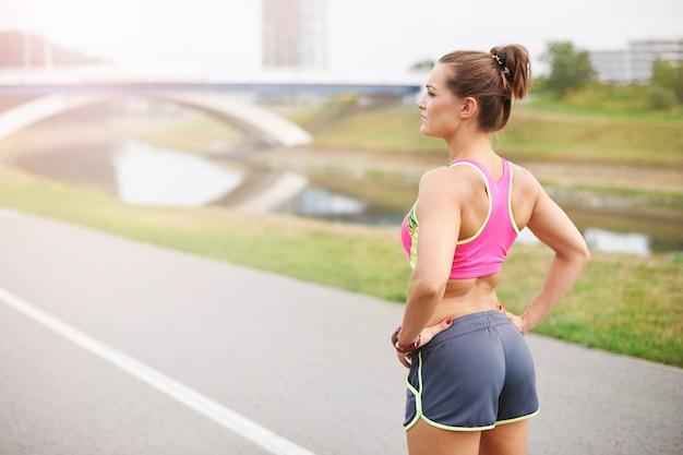 屋外で運動する若い女性。深呼吸して、彼女はジョギングの準備ができています
