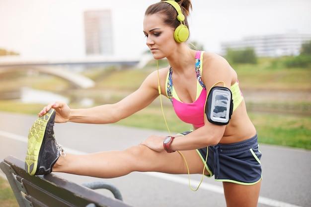 屋外で運動する若い女性。怪我をしないようにストレッチをする