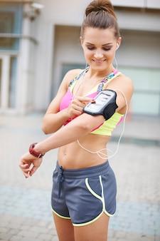 屋外で運動する若い女性。好きな音楽は素晴らしい仲間です