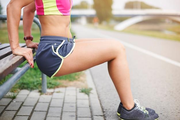 야외 운동하는 젊은 여자. 윗몸 일으키기와 다양한 스트레칭 운동