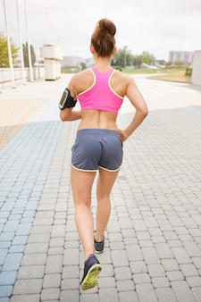 Giovane donna che si esercita all'aperto. trovare l'obiettivo è fondamentale per fare jogging