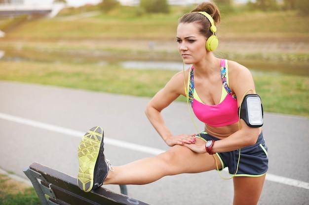 야외 운동하는 젊은 여자. 공원에서 벤치에서 스트레칭 초점 여자