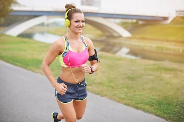 屋外で運動する若い女性。良い音楽と私はどこでも走ることができます