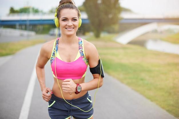 屋外で運動する若い女性。川沿いでジョギングに行くのにいい天気