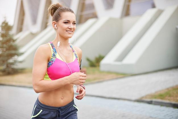 屋外で運動する若い女性。素晴らしい音楽と私はどこでも走ることができます
