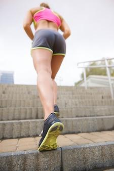 屋外で運動する若い女性。ハードトレーニングは成功への鍵です