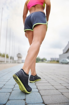 屋外で運動する若い女性。ハードトレーニング前の人間の足