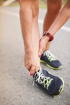屋外で運動する若い女性。怪我はいつでもあなたに起こる可能性があります