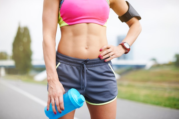 屋外で運動する若い女性。ジョギングは筋肉の構築に役立ちます