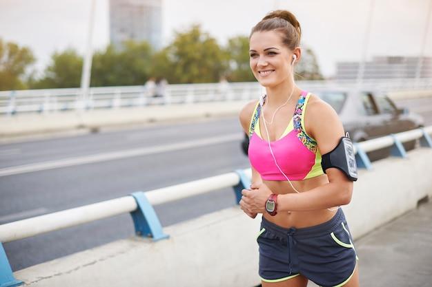 屋外で運動する若い女性。ジョギングは私の情熱であるだけでなく、ライフスタイルでもあります