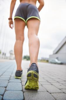 屋外で運動する若い女性。走っている女性の低いセクション
