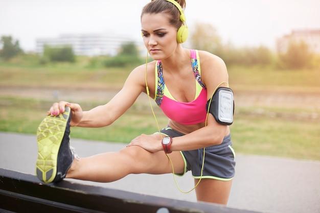 屋外で運動する若い女性。朝のジョギングは日中生き生きと感じさせます