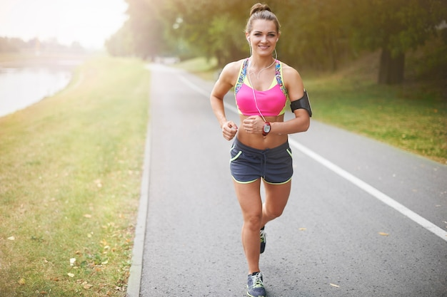 屋外で運動する若い女性。朝のランニングは一日中元気になります
