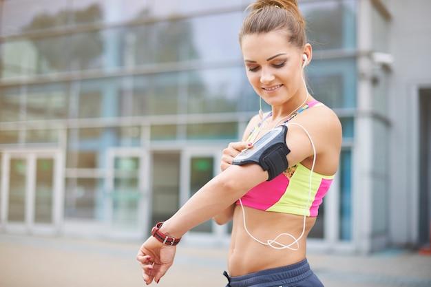 屋外で運動する若い女性。ジョギング中の音楽は素晴らしいヘルパーです