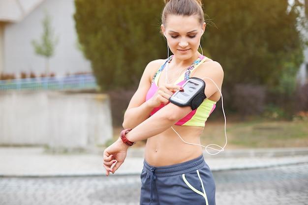 屋外で運動する若い女性。私の好きな音楽は私がスポーツをするのに役立ちます